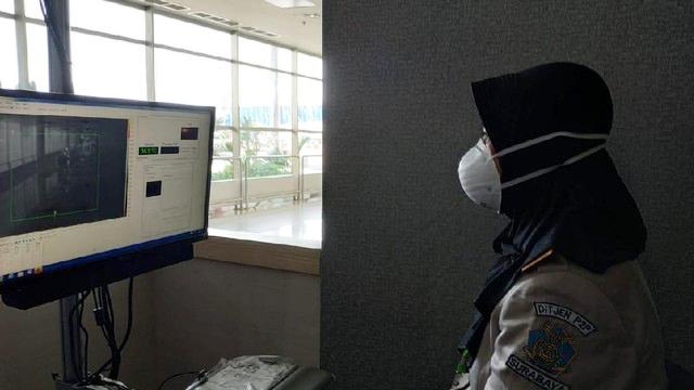 Petugas sedang memantau suhu tubuh penumpang di Bandara Juanda